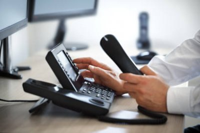 Contact us - businessman picking up phone to dial
